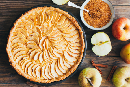 Freshly baked apple pie tart with custard filling on a rustic wooden table. Top view