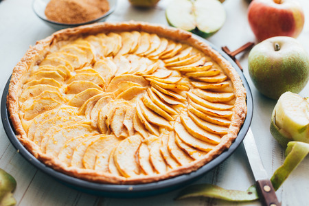 Freshly baked apple pie tart with custard filling on a rustic white wooden background