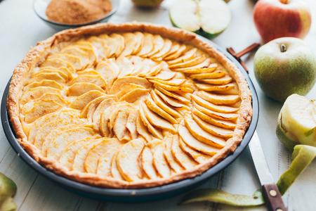Torta di mele appena sfornata con ripieno di crema pasticcera su un fondo di legno bianco rustico Archivio Fotografico