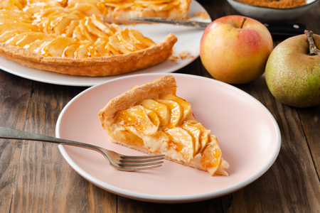 Portion of homemade apple pie tart with custard filling on a pink dish on a rustic wooden background Stok Fotoğraf