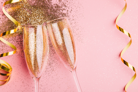 Two glasses of champagne toasting with golden confetti, glitter and serpentine on a pink background. Flat lay. Night of celebration concept