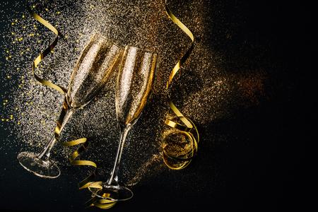 Due bicchieri di champagne che tostano con coriandoli dorati, glitter e serpentine su uno sfondo scuro. Lay piatto. Notte di celebrazione del concetto