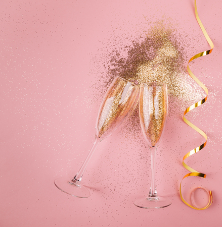 Two glasses of champagne toasting with golden confetti, glitter and serpentine on a pink background. Flat lay. Night of celebration concept Stockfoto - 108473685