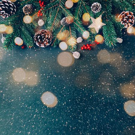 Kerstachtergrond met dennentakken, natuurlijke ornamenten en licht bokeh-effect Stockfoto