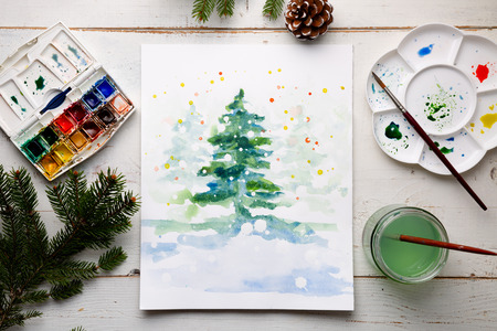 Handmade watercolor Christmas card on the work table with watercolor box, brushes, palette and fir branches and pine cones. Top view Stock fotó