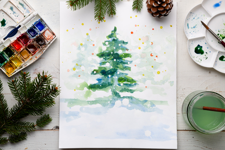 Handmade watercolor Christmas card on the work table with watercolor box, brushes, palette and fir branches and pine cones. Top view Stock Photo