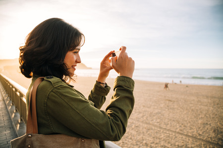 Young woman with green jacket taking picture with her mobile phone on the beach at sunset