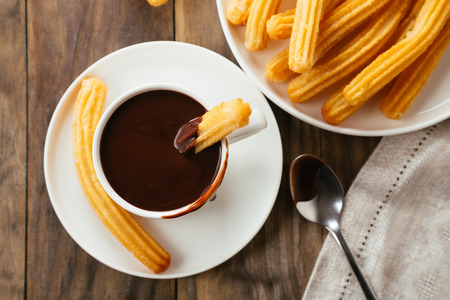Traditional spanish churros with hot chocolate sauce on a rustic wooden table. Top view 스톡 콘텐츠