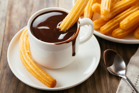 Traditional spanish churros with hot chocolate sauce on a rustic wooden table 写真素材 - 112463478