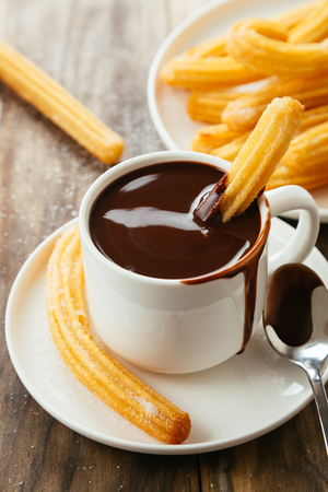 Traditional spanish churros with hot chocolate sauce on a rustic wooden table
