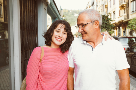 Mature father looking lovingly at her young daughter as the walk down the street Stockfoto - 117124139