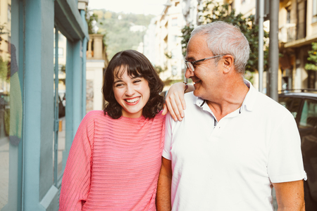 Mature father looking lovingly at her young daughter as the walk down the street. Focus on him Stockfoto - 117124172