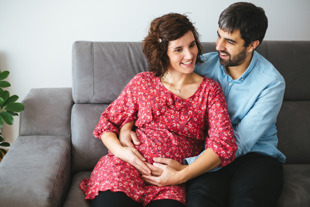 Happy pregnant couple embracing lovingly on the couch at home Stockfoto - 117124184