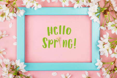 Hello spring text with the i made of a flower inside an empty turquoise picture frame on a pink background surrounded by cherry blossom and petals. Flat lay