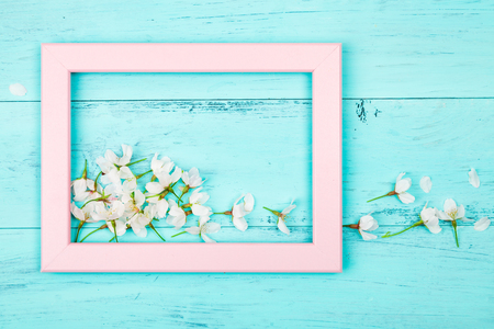 Cherry blossom flowers inside an empty pink picture frame on turquoise wooden planks. Flat lay