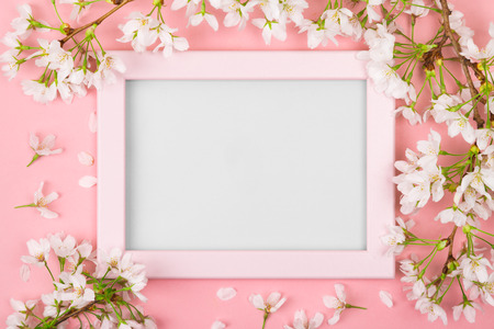 Spring background with an empty pink picture frame surrounded by white cherry blossom flowers and branches on a pink surface. Flat lay Foto de archivo - 117124235