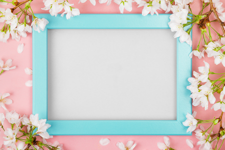 Spring background with an empty turquoise picture frame surrounded by white cherry blossom flowers and branches on a pink surface. Flat lay