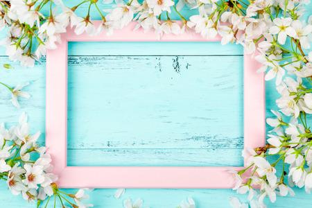 Fondo de primavera con un marco de imagen rosa vacío rodeado de flores de cerezo blanco y ramas sobre tablas de madera de color turquesa. Endecha plana Foto de archivo