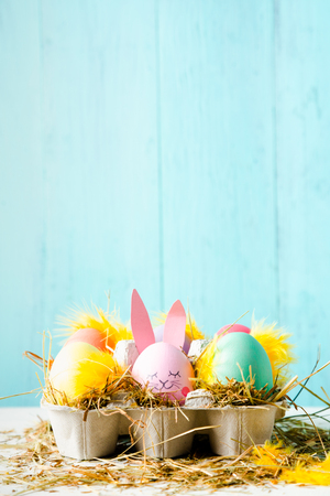 Cute and funny easter eggs with an egg decorated as a rabbit against a turquoise background, Vertical with copy space Stockfoto