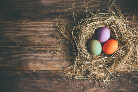 Dyed easter eggs in hay nest on a rustic wooden background. Top view