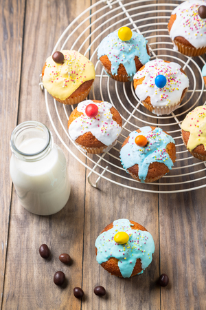 Easter or birthday cupcakes glazed with colorful sugar, sprinkles and chocolate with a bottle of milk for a kids party on a rustic wooden table