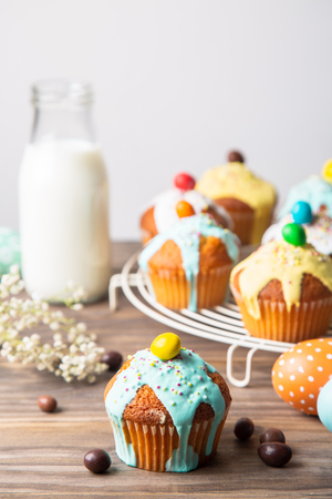 Easter cupcakes glazed with colorful sugar, sprinkles and chocolate with a bottle of milk and painted easter eggs  on a rustic wooden table Banco de Imagens