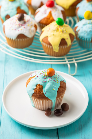 Easter or birthday cupcakes glazed with colorful sugar, sprinkles and chocolate for a kids party on a wooden turquoise table