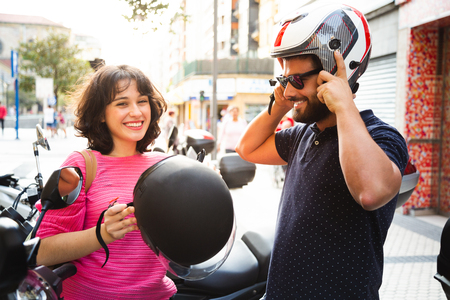 Happy and attractive young couple putting on their helmets to ride the motorcycle through the city