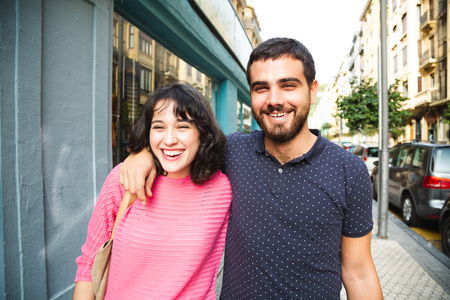 Happy and attractive young couple laughing while walking on the city street Фото со стока