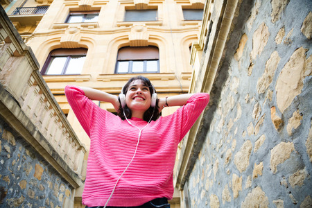 Happy young woman in pink sweater listening to music in the street. Low angle view 免版税图像
