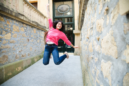 Happy young woman in pink sweater jumping when leaving home. Some blur beacuse of the movement Stock fotó
