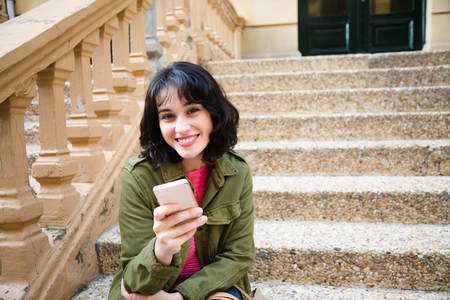 Happy young beautiful woman in green jacket using her smart phone sitting on stairs outdoors