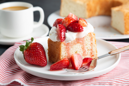 Portie engelvoedselcake geserveerd met slagroom en aardbeien Stockfoto