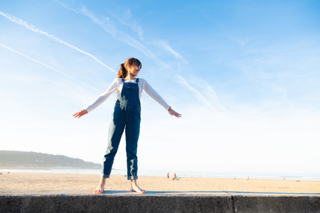 Happy little girl in overalls raising arms like a plane against the sky on the beach