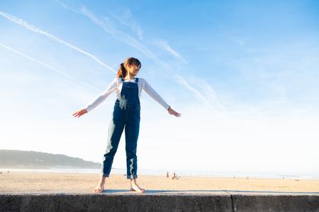Niña feliz en monos levantando los brazos como un avión contra el cielo en la playa