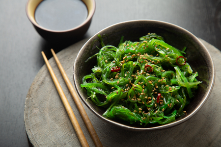 Wakame seaweed salad with sesame seeds and chili pepper in a bowl on a wooden slice Foto de archivo