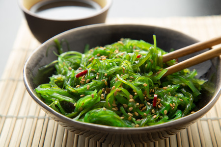 Wakame seaweed salad with sesame seeds and chili pepper in a bowl on a bamboo mat 写真素材