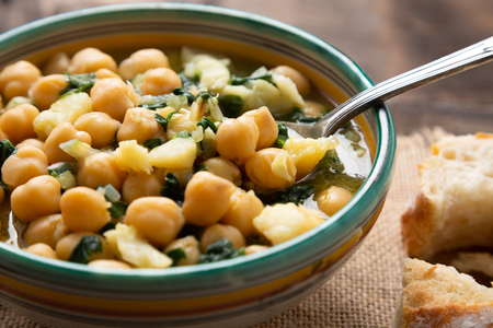 Chickpea soup with spinach and dry salted cod in a rustic bowl. Traditional spanish recipe in the Holy Week.