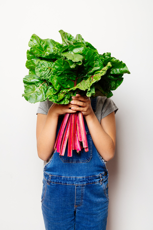 Little girl holding a bunch of fresh rainbow chard and hiding face behind the leaves