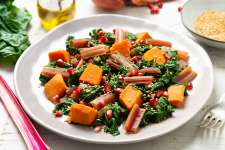 Boiled swiss chard with sweet potato, pomegranate and sesame seeds on a white wooden background