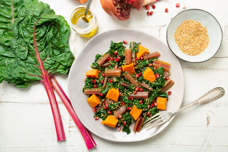 Boiled swiss chard with sweet potato, pomegranate and sesame seeds on a white wooden background. Top view