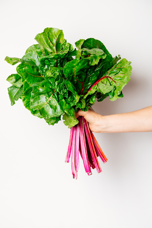 Hand of a woman holding a fresh bunch of swiss chard against a white background