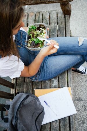 Midsection portrait of a student girl sitting in a bench while eating healthy salad with pasta in a glass lunch box
