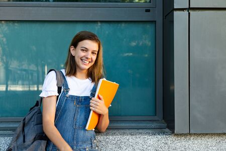 Portrait of a happy student girl leaning against the window of the school Foto de archivo - 130792185