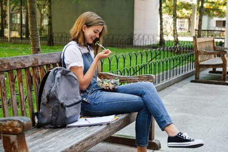 Chica estudiante en overoles de mezclilla con un almuerzo saludable mientras está sentado en un banco al aire libre Foto de archivo