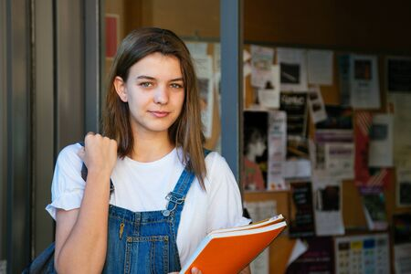 Portrait of a beautiful student girl at the school entrance with bulletin board at the background Foto de archivo - 130792212