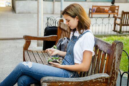 Chica estudiante en overoles de mezclilla con un almuerzo saludable mientras está sentado en un banco al aire libre