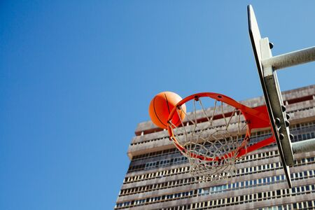 Basketball hoop with ball about to score against a blue sky and a skyscraper