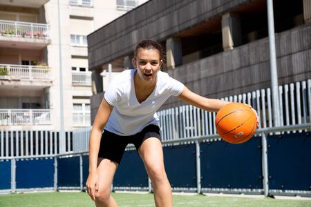 Teen girl playing basketball in an urban court Imagens