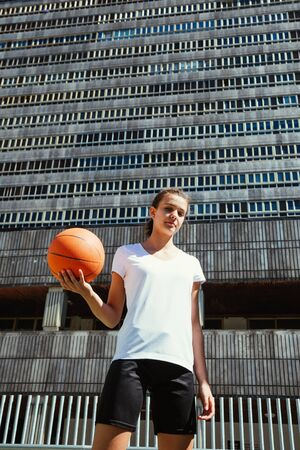 Portrait of a young female basketball player holding the ball against a heavy urban building 免版税图像